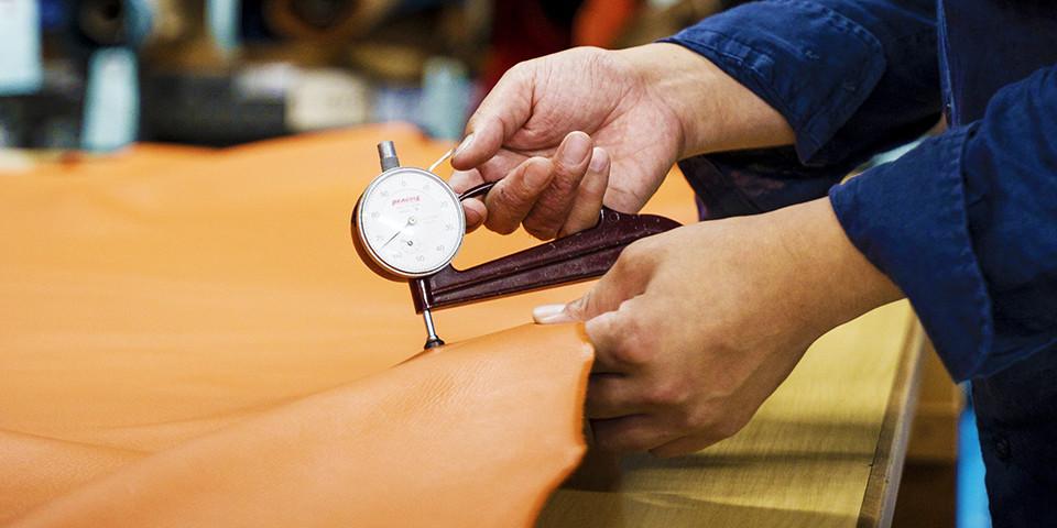 職人が革に計器を当てる様子